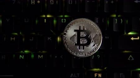 falsificação : The silver coin bitcoin lies on a computer keyboard that flashes green lights. Development of crypto currencies in virtual space. Stock Footage
