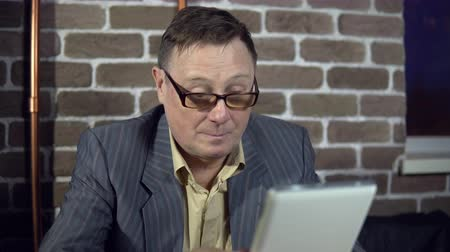 нетбук : Senior businessman in eyeglasses is working with a digital tablet at the office with a brick wall.