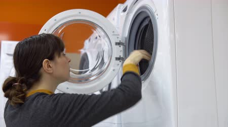 dvojitý : A young woman in a gray cardigan choosing washing machine in the shop of household appliances.