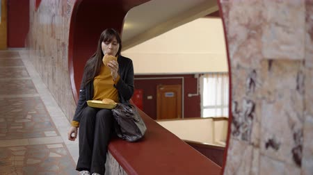recess : Young attractive woman eats a delicious hamburger in the office during lunch. The problem of healthy eating.