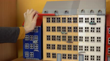maquette : A female architect is measuring a model of a house using a red pencil with divisions