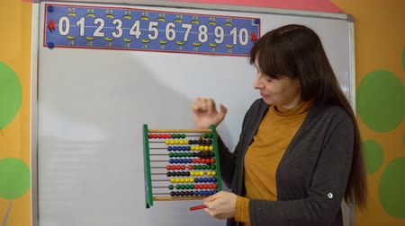 abacus : Beautiful young female teacher standing near blackboard in classroom in elementary school, she explains how to use the abacus.
