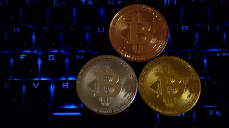 falsificação : Gold, silver, bronze, coins bitcoin lie on a computer keyboard that flashes blue lights. This shoot is a seamless loop. Stock Footage