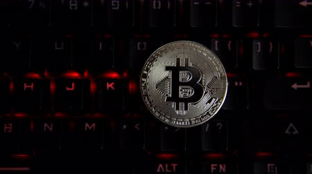 data mining : The silver coin bitcoin lies on a computer keyboard that flashes red lights. Development of crypto currencies in virtual space. Stock Footage
