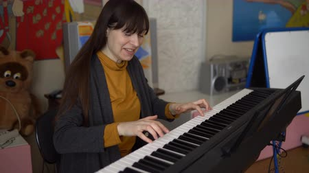 intéz : Portrait of a young happy woman pressing the keys of a digital piano, she enjoys the melody received thanks to a musical instrument.