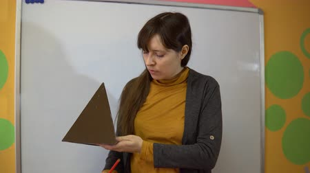 репетитор : Beautiful young female teacher standing near blackboard in classroom in elementary school, she shows the sides of the pyramid.