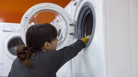 suszarka : A young woman in a gray cardigan choosing washing machine in the shop of household appliances.