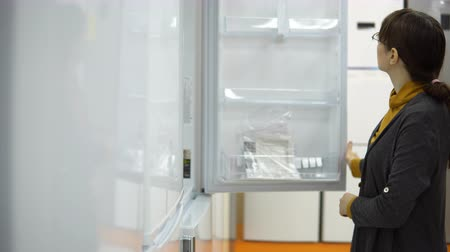 supermarket shelf : A young woman in a gray cardigan chooses a new two-compartment refrigerator in a home appliance store.