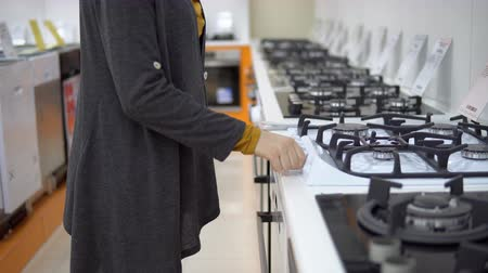 gas hob : A young woman in a gray cardigan choosing large gas stove in the shop of household appliances. Stock Footage