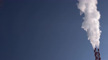 ısıtma : White smoke rises from the striped pipe into the blue cloudless sky on a bright, sunny day.