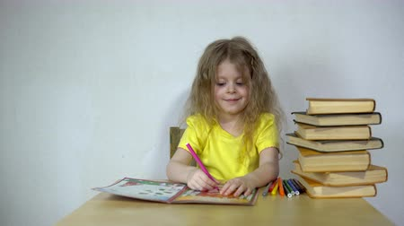 biblioteca : Small girl studying with books on table, she doing homework. Cute child draws with felt-tip pens in a special notebook learning his lessons at home, back to school.