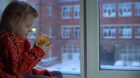 sill : A little pretty girl in a red fleece sweatshirt sits on the windowsill looking at the snowy cityscape.