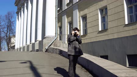 film camera : Young woman tourist in vintage gray coat photographing architecture in empire style on retro camera.