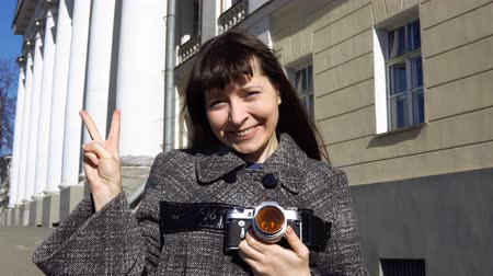 film camera : Young woman tourist in vintage gray coat photographing architecture in empire style on retro camera. A happy woman shows a sign of victory.
