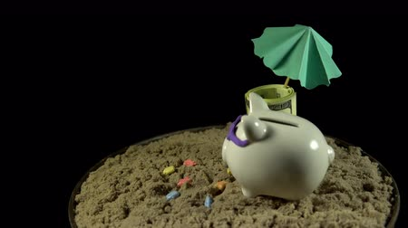dobrado : A white piggy bank in lilac sunglasses stands in the sand next to the folded one hundred dollar notes. The composition rotates on a black background, seamless loop shooting, 4K.