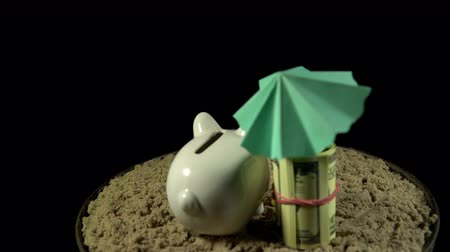 dobrado : A white piggy bank in sunglasses stands in the sand next to a umbrella, folded dollar bills. Someone puts small heart in the coin box. The composition rotates on a black background, loop shooting.