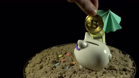 prase : A white piggy bank in sunglasses stands in the sand next to a umbrella, folded with 100 dollar bills. Someone puts bitcoin in the coin box. The composition rotates on a black background, loop shooting