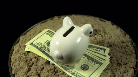 sand paper : A white piggy bank stands on a pack of dollars in the sand in front of a miniature football. The composition rotates on a black background, seamless loop shooting, 4K.