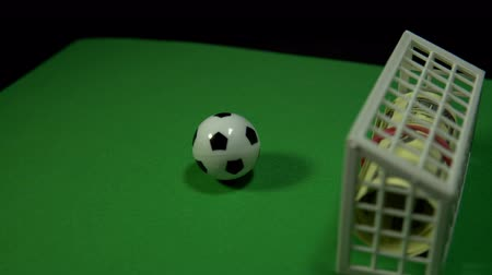 bribe : A miniature football ball stands on a green field opposite the gate with a bundle of dollars. The composition rotates on a black background, seamless loop shooting, 4K.