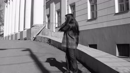 film camera : Young woman tourist in vintage gray coat photographing architecture in empire style on retro camera,black and white shooting. Stock Footage