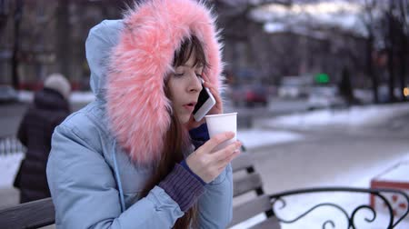 snow caps : A young woman in a gray warm jacket talking on the phone and drinking hot tea or coffee from a paper cup, a brunette sitting on a bench outside in the winter. Stock Footage
