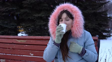 warms : A young woman in a gray warm jacket drinking hot tea or coffee from a paper cup, a brunette while sitting on a bench in a city park next to fir-trees on a snowy winter day.