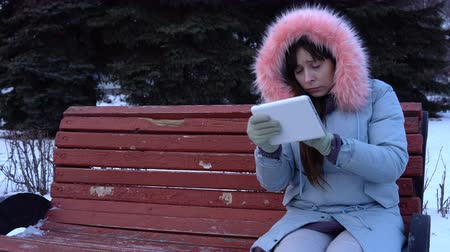 zarmoucený : A young sad, upset woman in a gray warm coat sits on a bench, uses a digital tablet and dances, in a city park next to fir-trees on a snowy winter day.