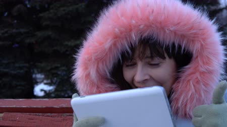 great video : Portrait of a young happy woman uses a digital tablet and sitting on a bench in a city park next to a Christmas tree on a snowy winter day. Stock Footage