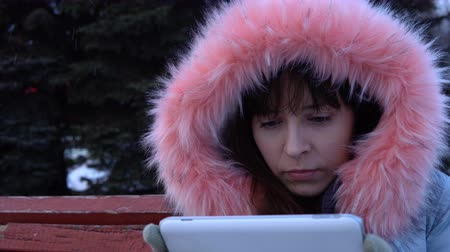 пораженный : Portrait of a young astonished woman uses a digital tablet and sitting on a bench in a city park next to a Christmas tree on a snowy winter day.