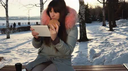 блог : A young woman blogger in a gray warm parka sits on a bench, uses a digital tablet and drinking hot tea or coffee from a paper cup, in a city park on a snowy winter day.