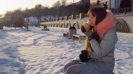 навынос : Portrait of a young woman eating a burger and enjoying the application in a smartphone to create content for her blog, sitting on a bench in winter during sunset.