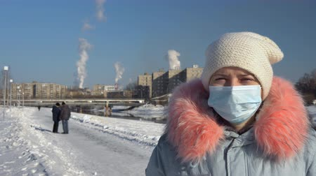 metallurgical plant : A young woman wears a face mask and a gray parka, she stands against a background of pipes of a metallurgical plant on a winter day.