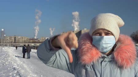 metallurgical plant : Blogger wearing a protective mask and a gray parka records video on the phone and stands on a background of pipes of a metallurgical plant on a winter day. A young woman is showing a thumbs-down. Stock Footage