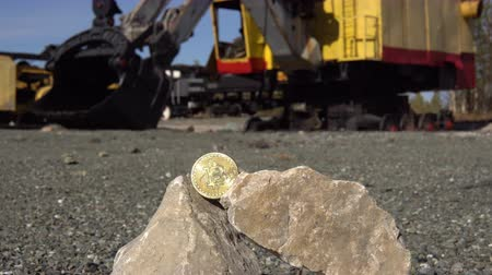 monety : Gold bitcoin on stones in a quarry against the background of a mining excavator, dolly shoot.