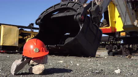 taş ocağı : The golden bitcoin stands on an orange helmet against the background of a large bucket of a mining excavator.