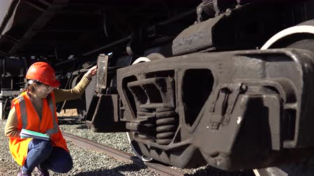 train workers : A young brunette woman railway worker in an orange vest checks the hitch unit of the freight wagon, raises the lid of the axle-box with a plain bearing and compares it with the scheme.