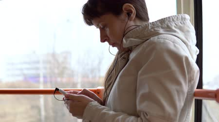fone de ouvido : A woman is riding in a tramcar and listening to music on headphones on a smartphone. The female passenger is standing by the window next to the orange handrails. Vídeos