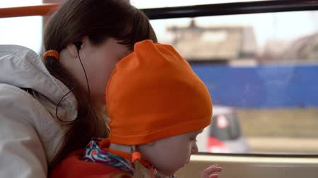 fone de ouvido : Mother and daughter ride together in a tram listening to music on headphones and using a smartphone.