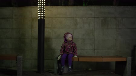 neglected : A little girl is sitting on a bench under the light of a lantern at night in a park. The child is lost, worried and waiting for the parents. Stock Footage