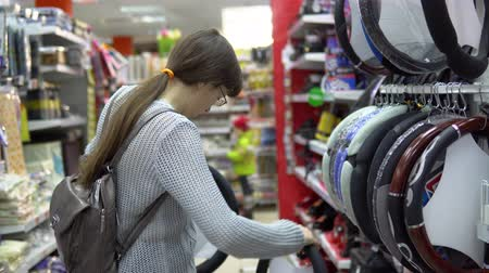 spare part : A young woman chooses automobile steering wheel cover in the department of accessories and spare parts for autos. Stock Footage