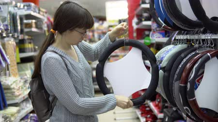 removable : A young woman chooses automobile steering wheel cover in the department of accessories and spare parts for autos. Stock Footage