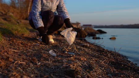activist : A young female volunteer collects garbage on the shore of the reservoir in the evening at sunset in early spring or autumn.