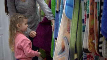 felpudo : Mom and sweet little daughter choose a rug, they compare different carpets by color and softness.