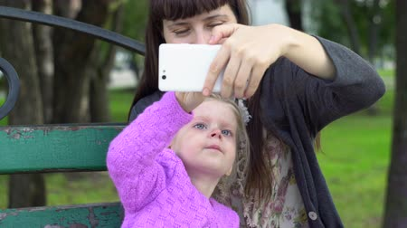 блог : Mom with daughter are doing selfie or make a video call, the family shares their good mood with the person using the smartphone. Стоковые видеозаписи