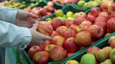 supermarket food : Someone selects apples in the supermarket. Female hand chooses red fruits in the vegetable department at the grocery store.