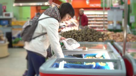 потребитель : A young woman chooses a green frozen string bean in a self-service store. A girl is buying vegetables in a supermarket.
