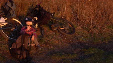 kask : Little happy girl in sunglasses and helmet sitting next to bicycle and showing thumbs up in the evening at sunset. Stok Video