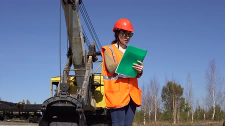 vest : A young woman worker in sunglasses stands near a mining excavator, looking over project.