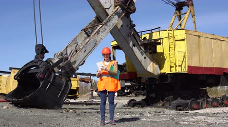 taş ocağı : A young worker in an orange waistcoat and a helmet stands near a mining excavator and uses a digital tablet.