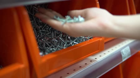 fasteners : Close-up of a hand takes an orange container from a tapping screw. Selection and purchase of building materials in the hypermarket.